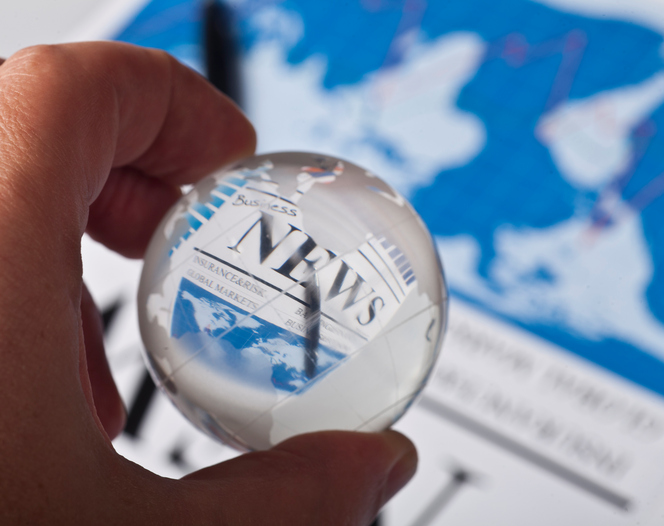 Hand holding glass globe on business documents background.